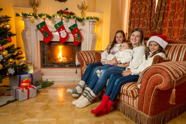 Feliz joven madre sentada con sus hijas en el sofá salón junto a la chimenea en navidad