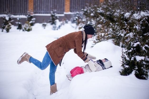 Feliz joven madre con su pequeña hija linda divirtiéndose en el patio trasero en un día de invierno