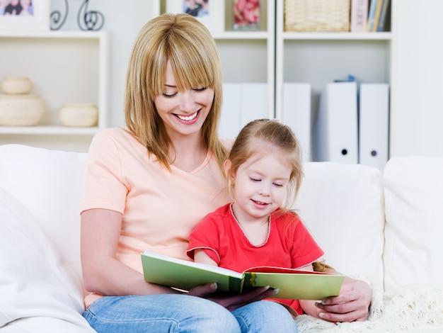 Feliz joven madre con su pequeña hija sonriente leyendo el bood juntos - en el interior