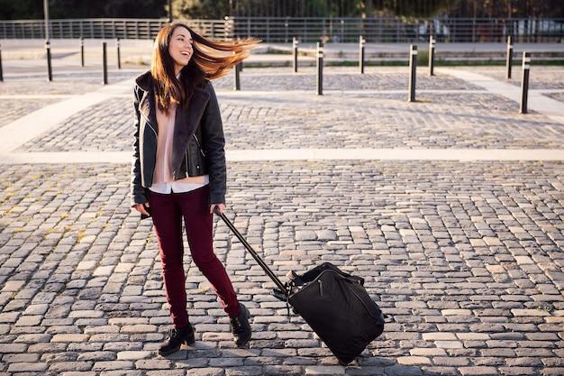Feliz joven con maleta caminando por la calle