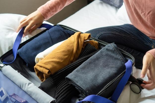 Feliz joven manos empacando ropa en equipaje de viaje en cama