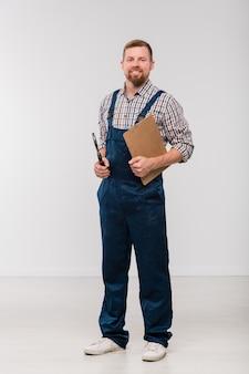 Feliz joven mecánico barbudo en overoles y camisa sosteniendo el portapapeles con documento y herramienta de mano mientras está de pie en aislamiento