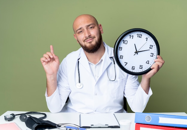 Feliz joven médico calvo vestido con bata médica y un estetoscopio sentado en el escritorio de trabajo con herramientas médicas sosteniendo el reloj de pared y apunta hacia arriba aislado sobre fondo verde