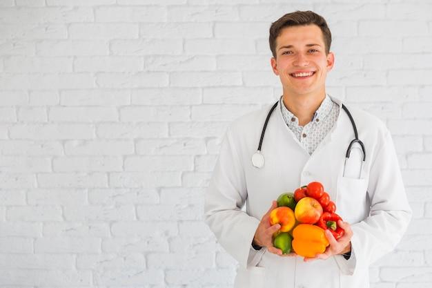 Feliz joven médico masculino de pie contra la pared con frutas frescas y vegetales