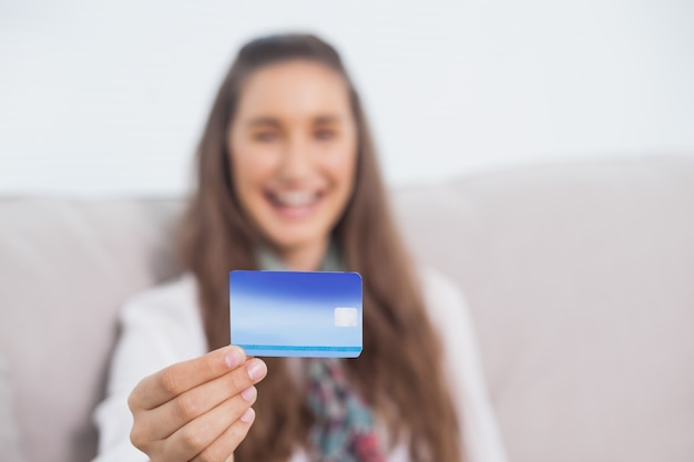 Feliz joven modelo con su tarjeta de crédito
