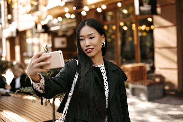 Feliz joven morena en elegante gabardina negra sonríe sinceramente, sostiene el teléfono y toma selfie afuera cerca de la cafetería de la calle