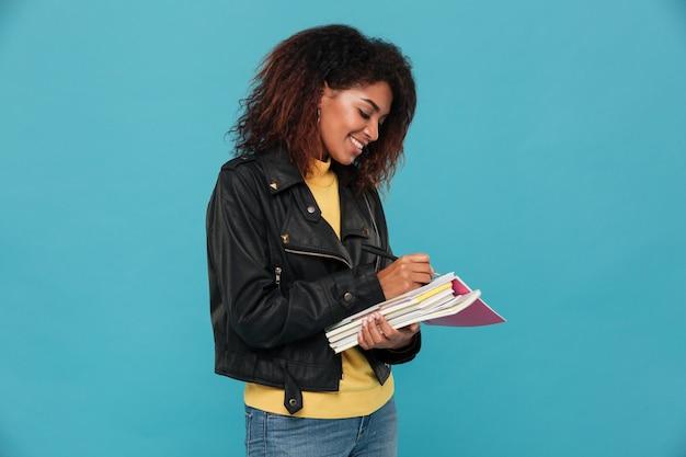 Feliz joven mujer africana estudiante escribiendo notas.