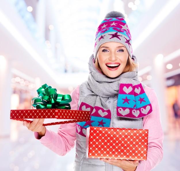 Feliz joven mujer americana con un regalo de navidad en una ropa de abrigo de invierno
