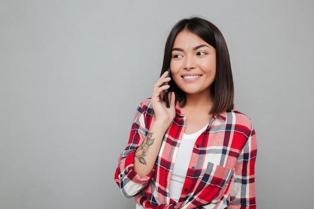 Feliz joven mujer asiática aislada sobre pared gris