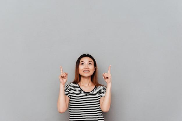 Feliz joven mujer asiática de pie sobre la pared gris apuntando