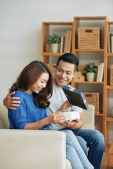 Feliz joven mujer asiática sentada en el sofá en casa y recibiendo presente del marido