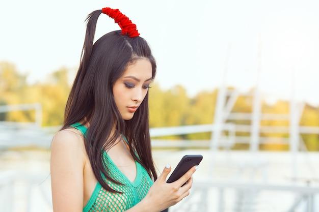 Feliz joven mujer asiática con smartphone de pie en la calle
