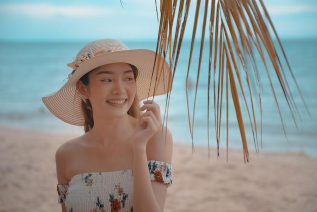 Feliz joven mujer asiática con sombrero caminando y relajarse en la playa de arena con felicidad.