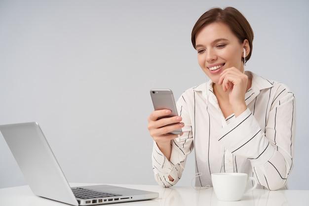 Feliz joven mujer de cabello castaño con corte de pelo corto de moda tocando suavemente su barbilla con la mano levantada y sonriendo alegremente mientras mira la pantalla de su teléfono inteligente