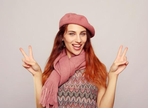 Feliz joven mujer caucásica haciendo pulgar arriba signo y sonriendo alegremente, mostrando su apoyo y respeto a alguien. lenguaje corporal.