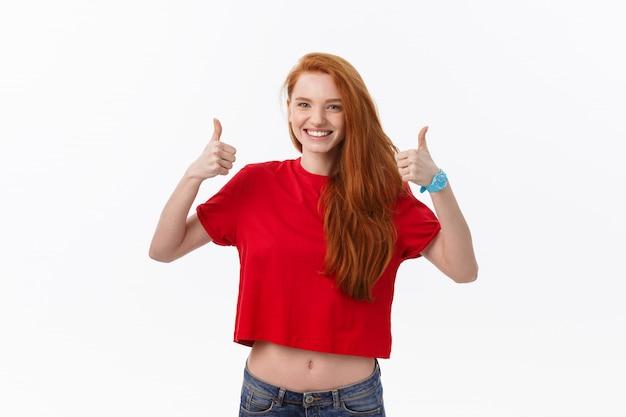 Feliz joven mujer caucásica haciendo pulgar arriba signo y sonriendo alegremente, mostrando su apoyo y respeto a alguien.