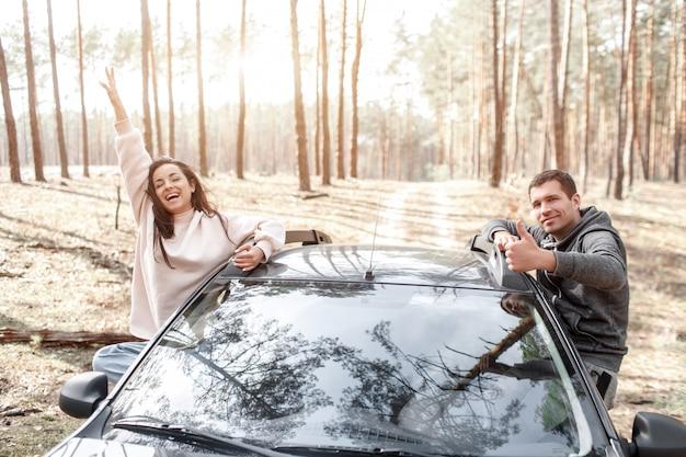 Feliz joven mujer y hombre salieron de la ventana de un automóvil. viajando en coche por el bosque. viaje de campo. vacaciones en coche