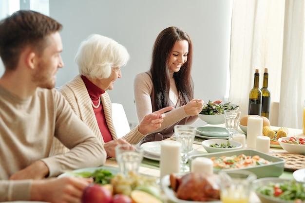 Feliz joven mujer morena poniendo ensalada en el plato de la abuela sentada junto a ella por la mesa festiva servida para la cena familiar