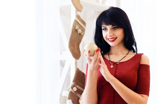 Feliz joven mujer morena en vestido rojo con una bola de navidad en una habitación de año nuevo decorado.