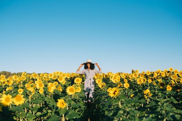 Feliz joven mujer negra caminando en un campo de girasol