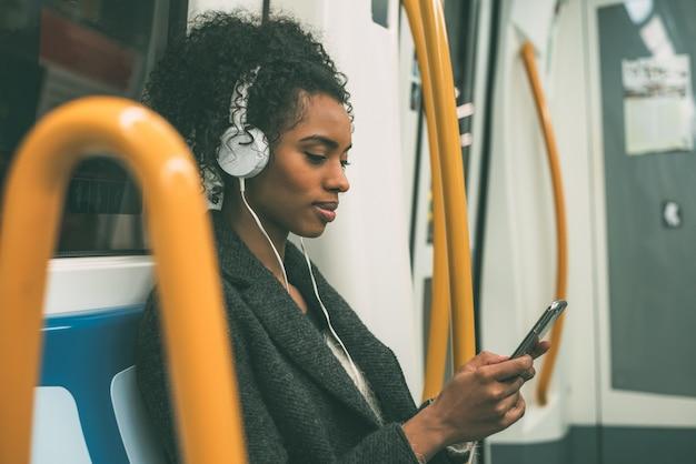 Feliz joven mujer negra sentada dentro del metro escuchando música