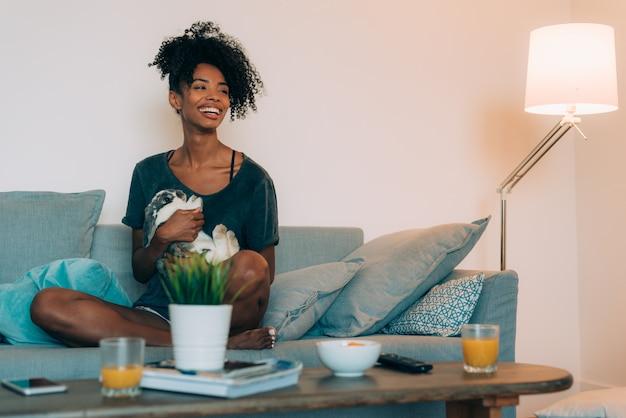 Feliz joven mujer negra sentada en el sofá dando cariño a un conejito