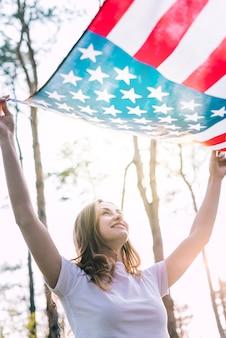 Feliz joven mujer ondeando bandera de estados unidos