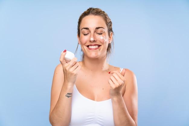 Feliz joven mujer rubia con crema hidratante sobre pared azul aislada