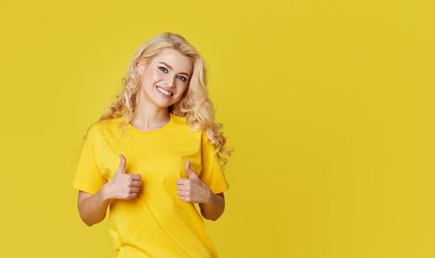 Feliz joven mujer rubia de pie sobre la pared amarilla
