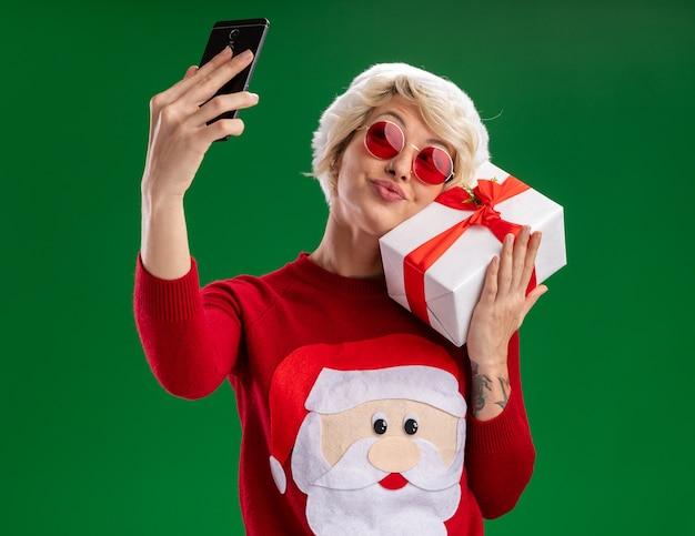 Feliz joven mujer rubia con sombrero de navidad y suéter de navidad de santa claus con gafas sosteniendo el paquete de regalo tocando la cara con ella tomando selfie aislado sobre fondo verde