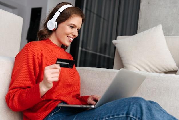 Feliz joven mujer vestida informalmente sentada en un piso en casa, usando la computadora portátil, celebrando el éxito, mostrando la tarjeta de crédito