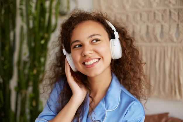 Feliz joven mulata rizada, sonríe ampliamente y escucha su canción favorita en auriculares, disfruta de la música y los domingos por la mañana, se ve feliz y contenta.