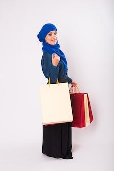 Feliz joven musulmana con bolsa de compras sobre fondo blanco.