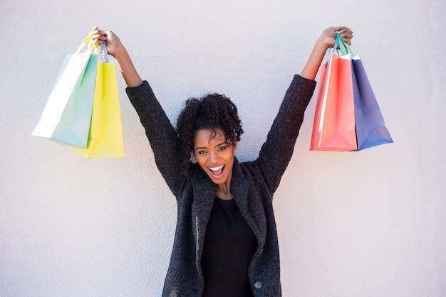 Feliz joven negra con bolsas de compras contra una pared blanca