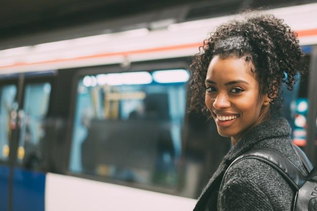Feliz joven negra dentro de la estación de metro esperando el tren