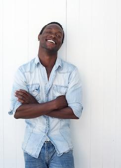 Feliz joven negro sonriendo al aire libre contra el fondo blanco