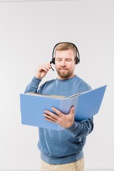 Feliz joven operador en auriculares mirando uno de los documentos en la carpeta mientras consulta a los clientes en línea de forma aislada