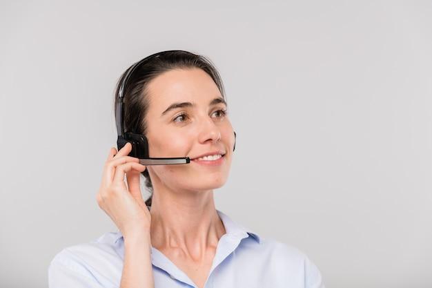 Feliz joven operador morena con auriculares hablando con clientes en línea frente a la cámara de forma aislada