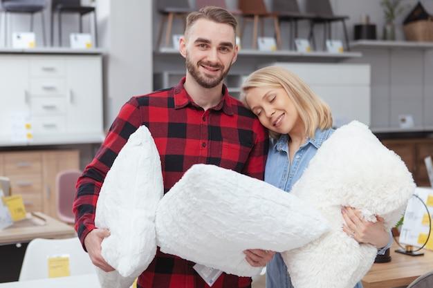 Feliz joven ouple comprar almohadas nuevas en la tienda de muebles