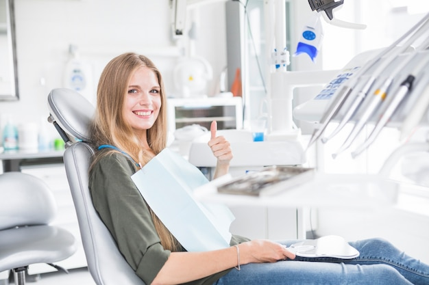 Feliz joven paciente femenino sentado en la silla dental gesticular signo bien