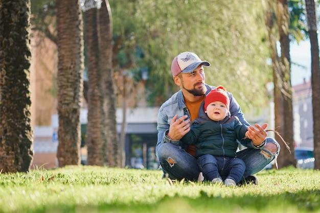 Feliz joven padre caminando con su pequeño hijo