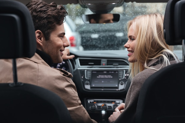 Feliz joven pareja amorosa en coche mirando el uno al otro.