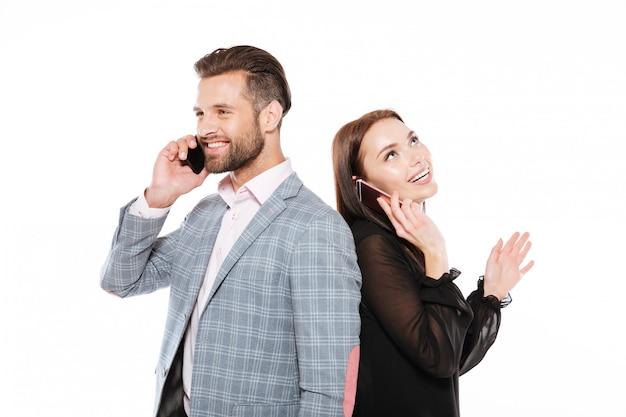 Feliz joven pareja amorosa hablando por teléfonos.