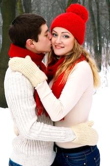 Feliz joven pareja amorosa en suéteres blancos y pañuelo rojo