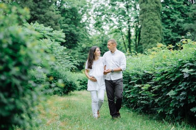Feliz y joven pareja embarazada abrazando en la naturaleza