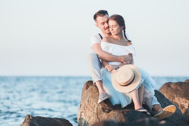 Feliz joven pareja romántica relajante en la playa y viendo el atardecer