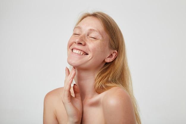 Feliz joven pelirroja guapa con maquillaje natural sonriendo alegremente con los ojos cerrados y tocando su cuello con la mano levantada, de pie sobre la pared blanca