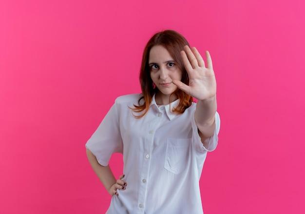 Feliz joven pelirroja sosteniendo la mano en la cadera y extendiendo la mano aislada en la pared rosa