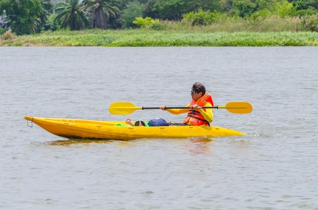 Feliz joven piragüismo en un lago