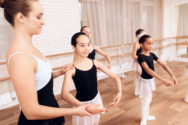 Feliz joven profesor de ballet entrena niños diligentes.